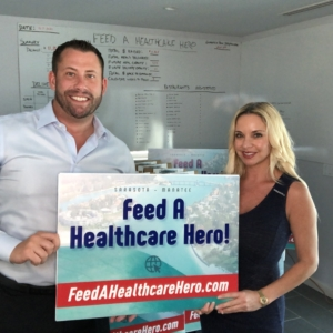 Brian Loebker and Brandy Coffey Holding Feed a Healthcare Hero Sign