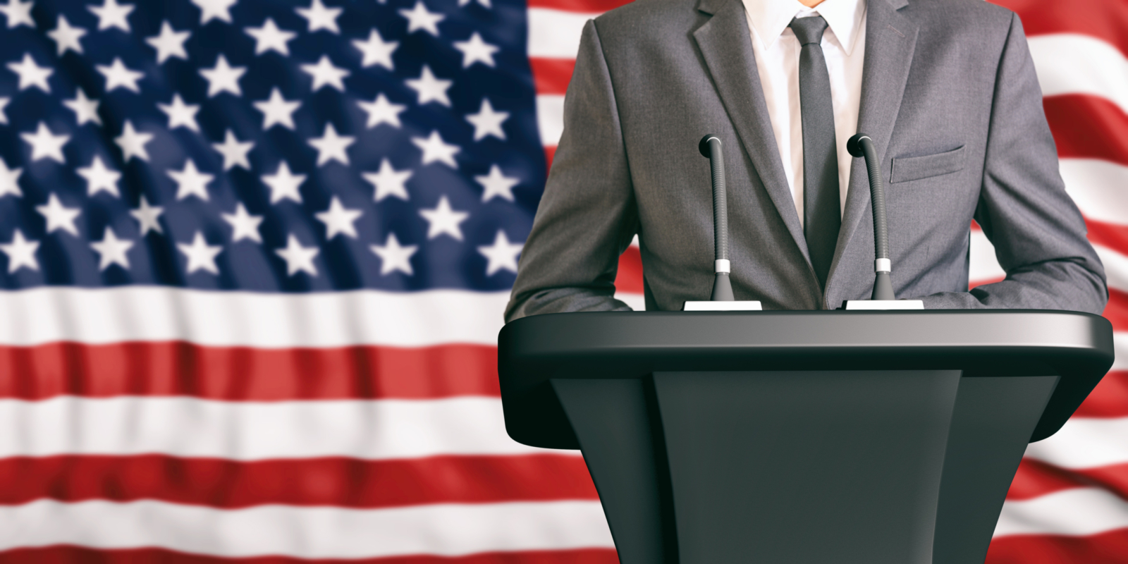 Guy standing in front of podium with American Flag in the background